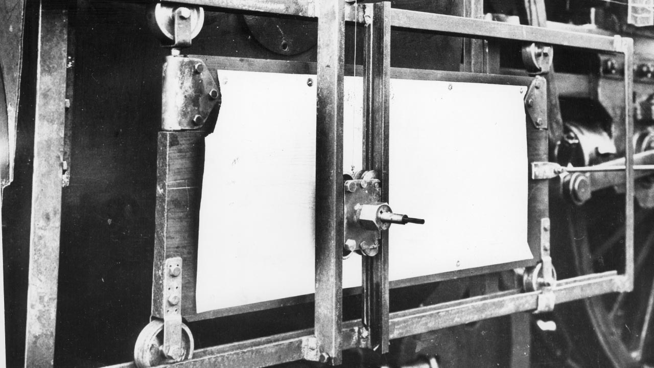 Pencil and paper attached to the drive shaft on a locomotive to record performance testing information 1930.