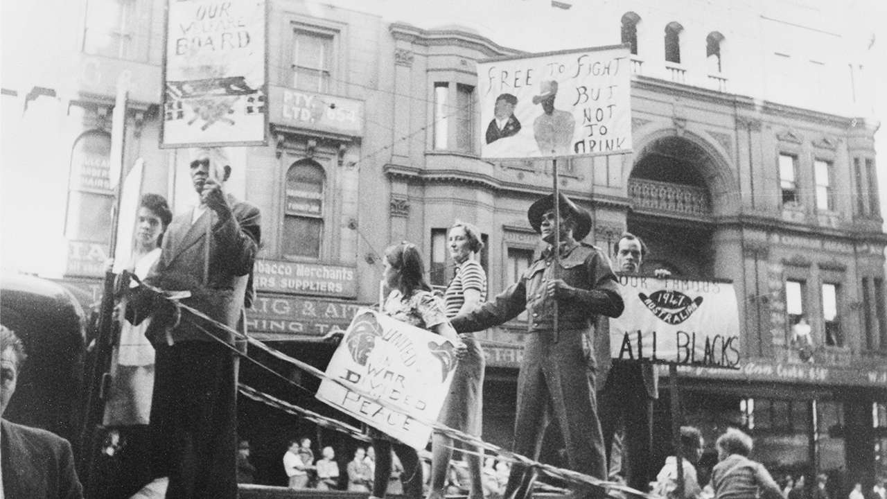 Herbert Groves, Aboriginal activist, spoke at Eveleigh during lunch meetings. His sign says 'Free to fight but not to drink' referring to discrimination against Aboriginal veterans who were not allowed into returned services venues, such as the RSL.