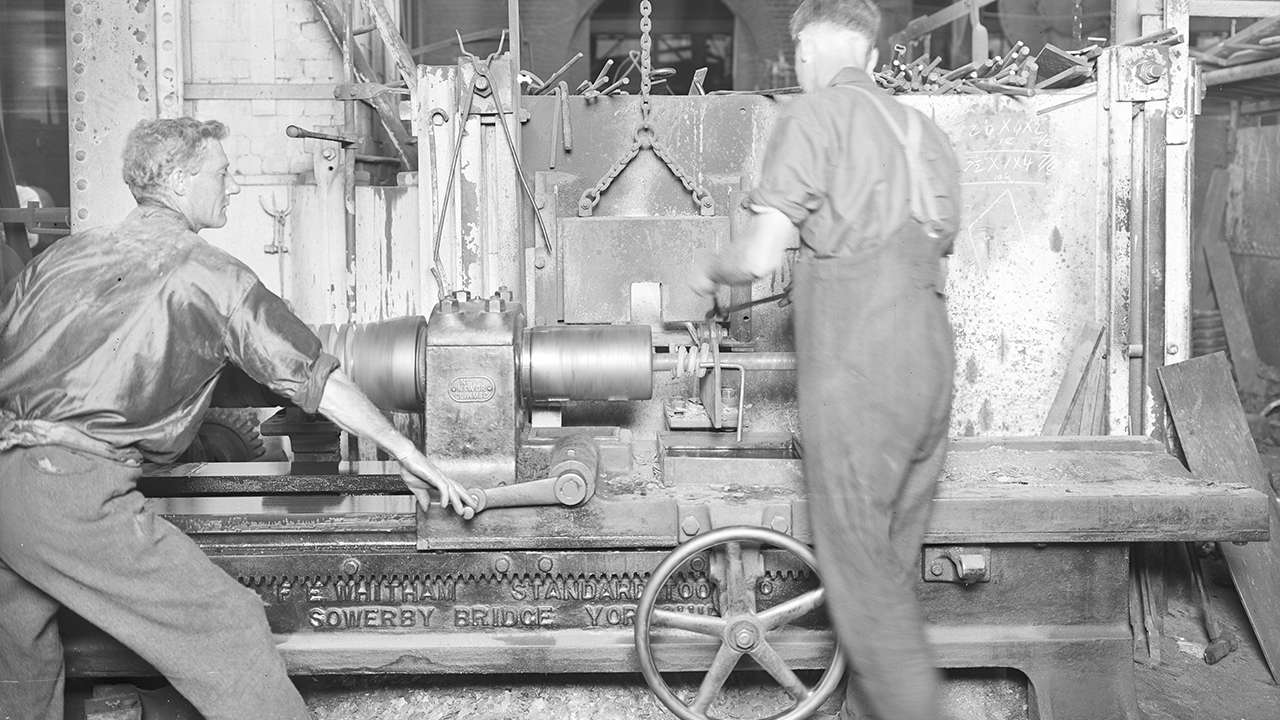 Forming a spring coil on the Whitham Spring Coiler in the old Spring Shop, circa 1920