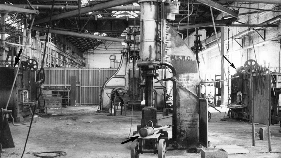 In 2003 the steam hammer sat silently. To the left and right furnaces are visible with spoked wheels that aided in opening the furnace. On the trolley is a ram which could swing from the roof and assist to jump up or shorten connecting rods.