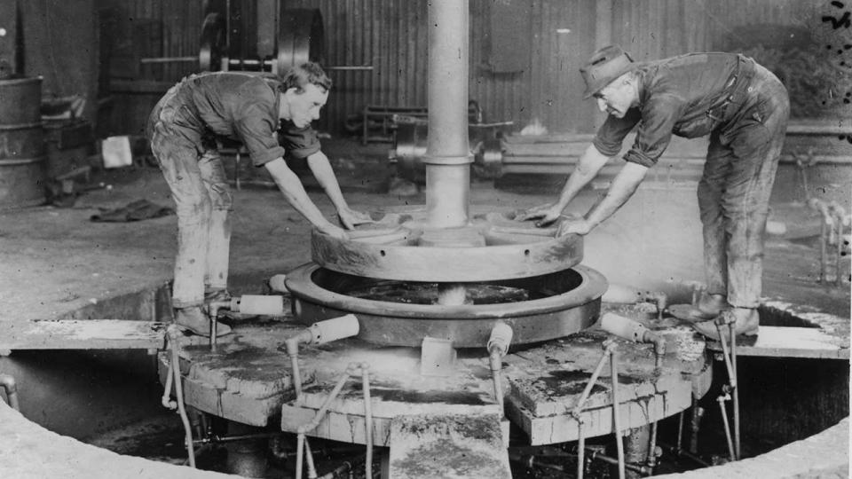 Moulders at work on driving wheel, undated