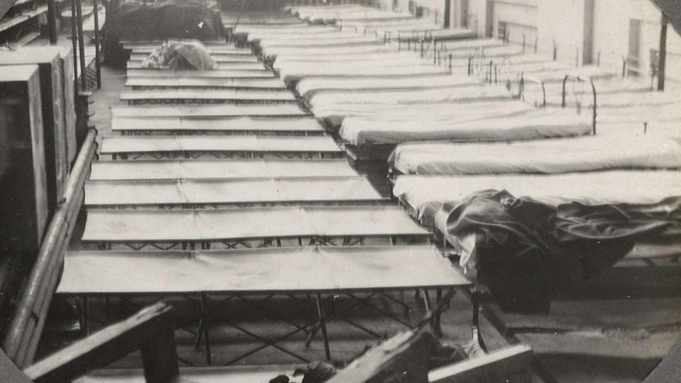 Rows of stretchers and beds set out in the Paint Shop at Eveleigh Workshops, August 1917. Non‐strikers and labour brought in from rural areas were housed at Eveleigh during the strike period
