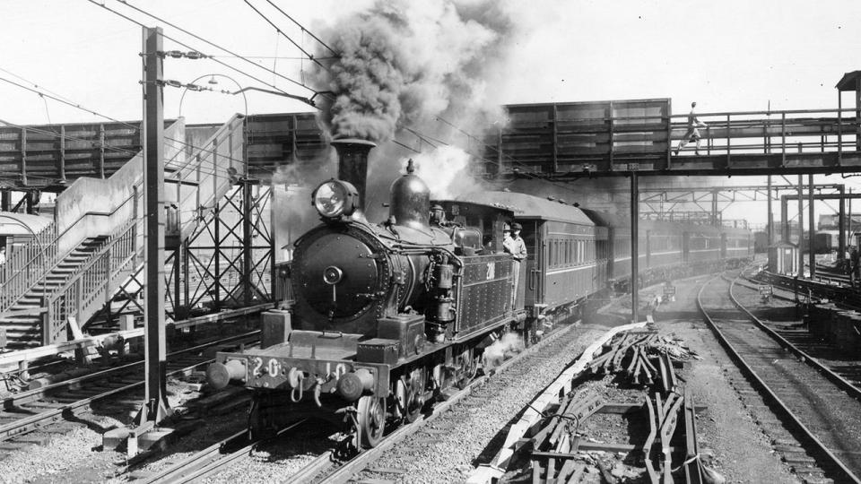 The last suburban steam train from Carlingford releases a hot blast of steam passing beneath the Eveleigh workshops footbridge near Redfern Station. 8 August 1959.